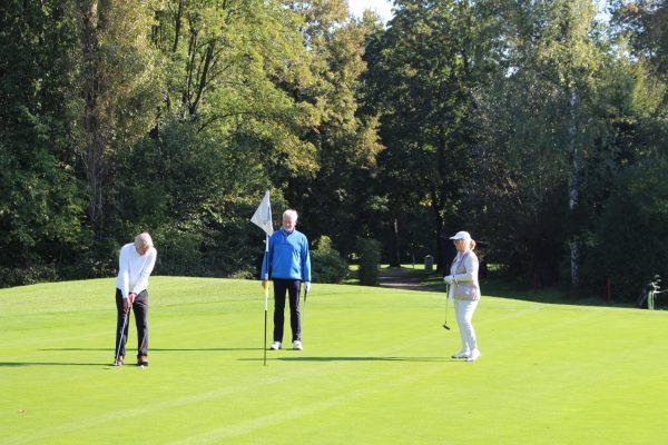 Drei Golfer auf dem Puttinggrün (Green)